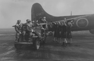 Thurleigh, 1942. A bomb crew of the 306th wave to Picture Post Girls in front of a B-17. (FRE 1162)