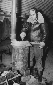 Sergeant Fred Dioquardo of the 303rd Bomb Group stoking the stove. (FRE 943)