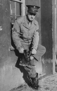 Corporal Edward J. Bowman of the 303rd Bomb Group cleaning his muddy boots. (FRE 1049)